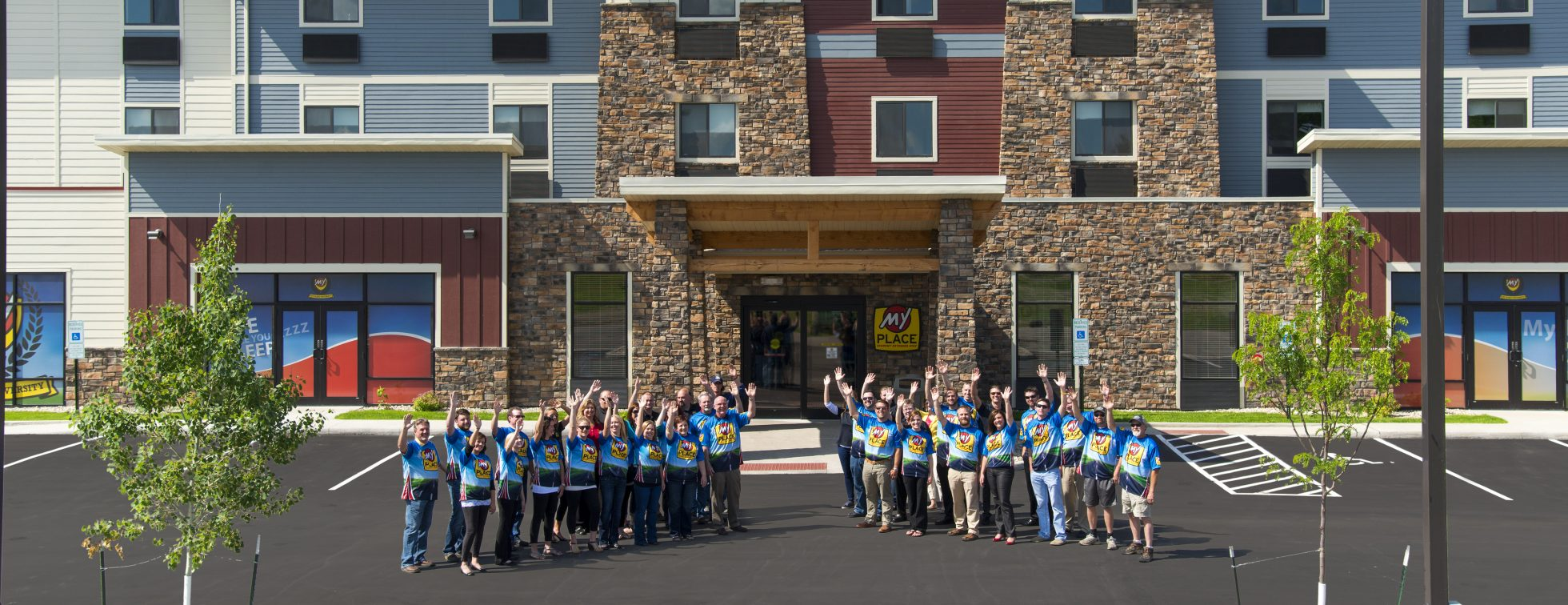 Several team members waving outside of a My Place Hotel