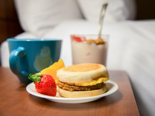 Breakfast in the room: coffee, fruit, yogurt, and breakfast sandwich